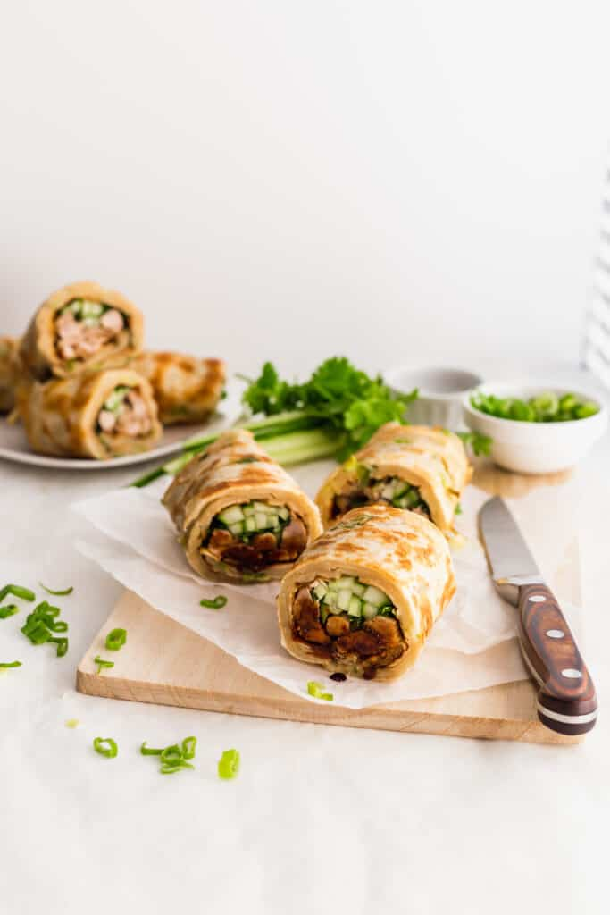 Cut turkey green onion pancake rolls on parchment paper on top of wooden board with knife, greens in background.