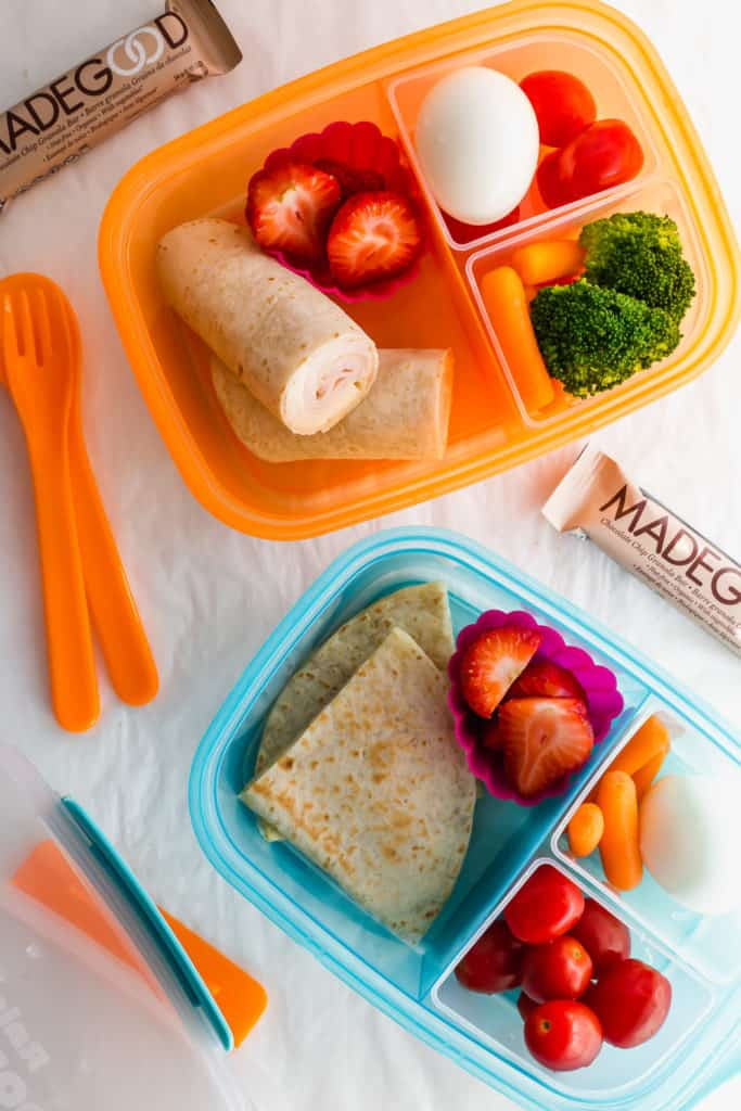 2 bento lunch boxes filled with fruit, veggies, tortillas.