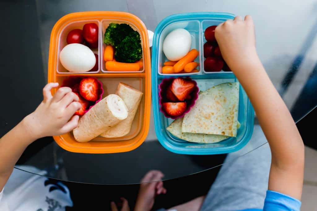 2 bento lunch boxes filled with fruit, veggies, tortillas with kids hands.