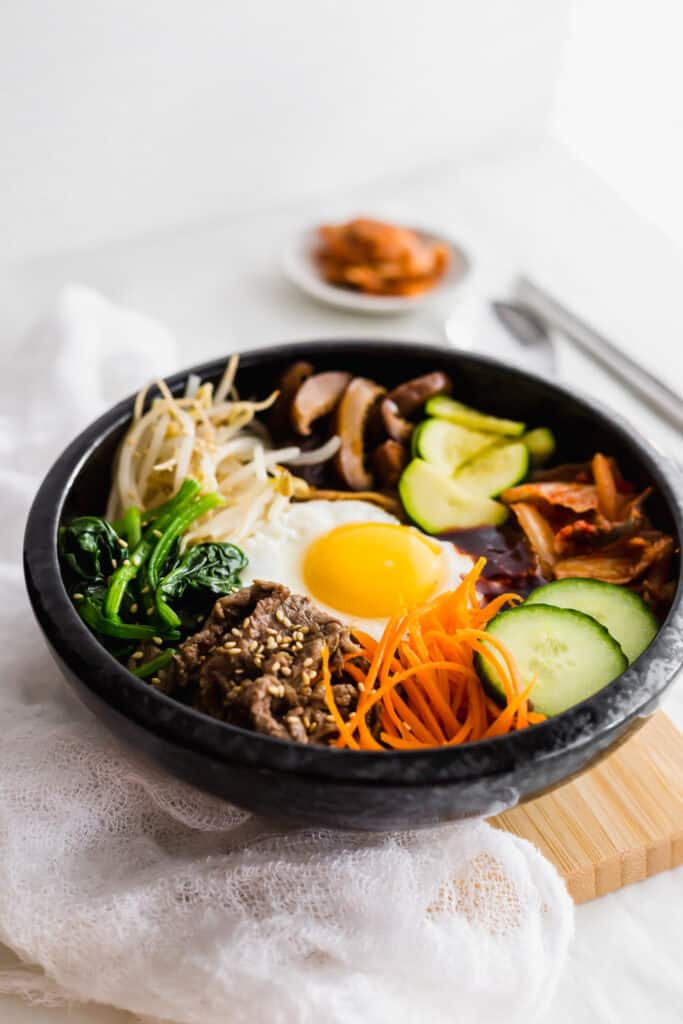 Close up of Korean bibimbap ingredients in a black bowl on wooden board with spoon, chopsticks, kimchi on the side.