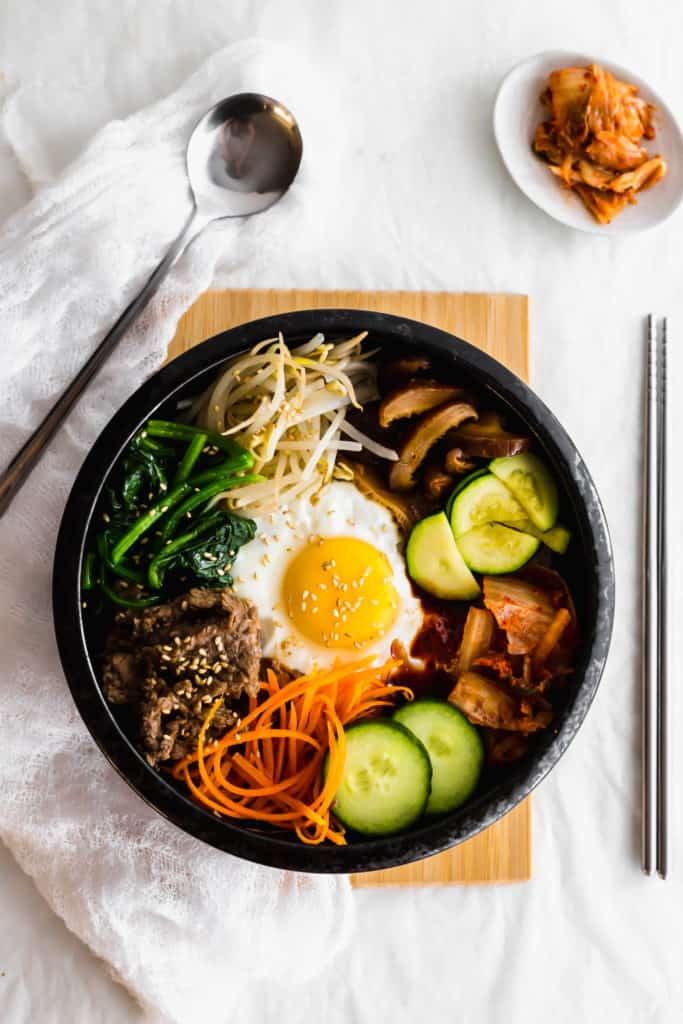 Korean bibimbap ingredients in a black bowl on wooden board with spoon, chopsticks, kimchi on the side.