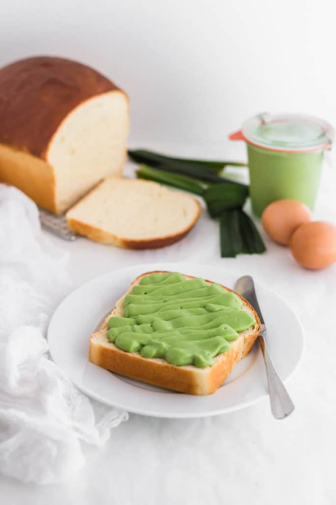 Green kaya pandan coconut jam on a slice of bread on white plate with knife, loaf of bread, eggs and pandan leaves in background.