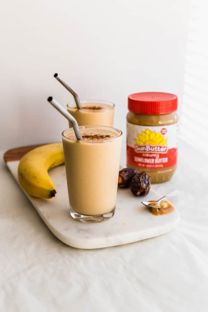Glasses of SunButter date smoothie with straws on marble, with banana, dates, SunButter jar on side.