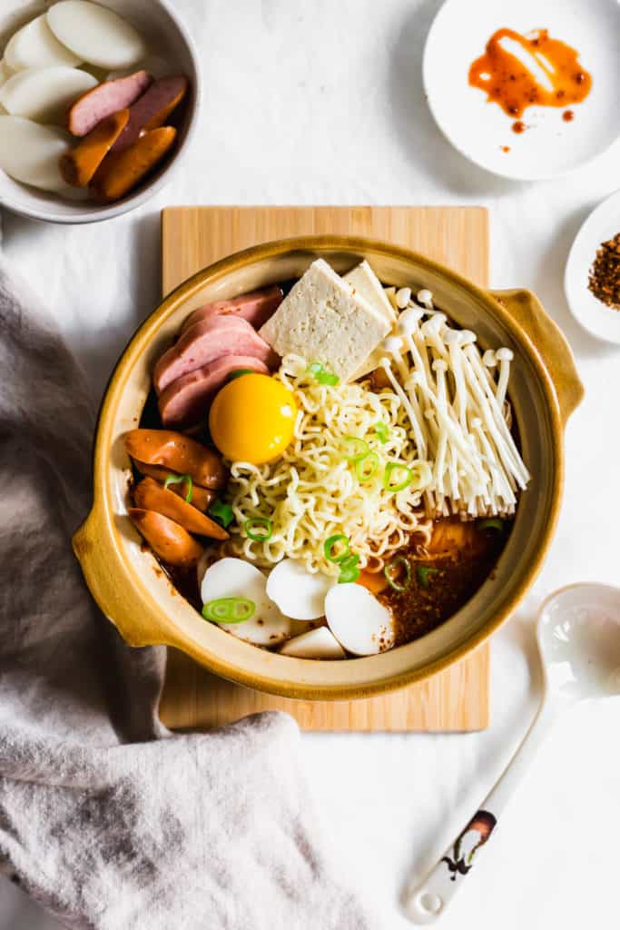 A stoneware pot filled with budae jiggae ingredients on wooden board with linen in front, ladle on side, extra ingredients in bowl.
