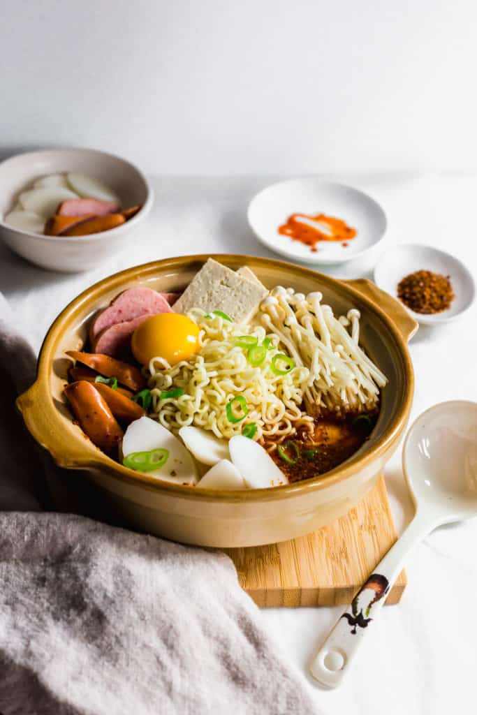 A stoneware pot filled with budae jiggae ingredients on wooden board with linen in front, ladle on side, ingredients in bowl in background..
