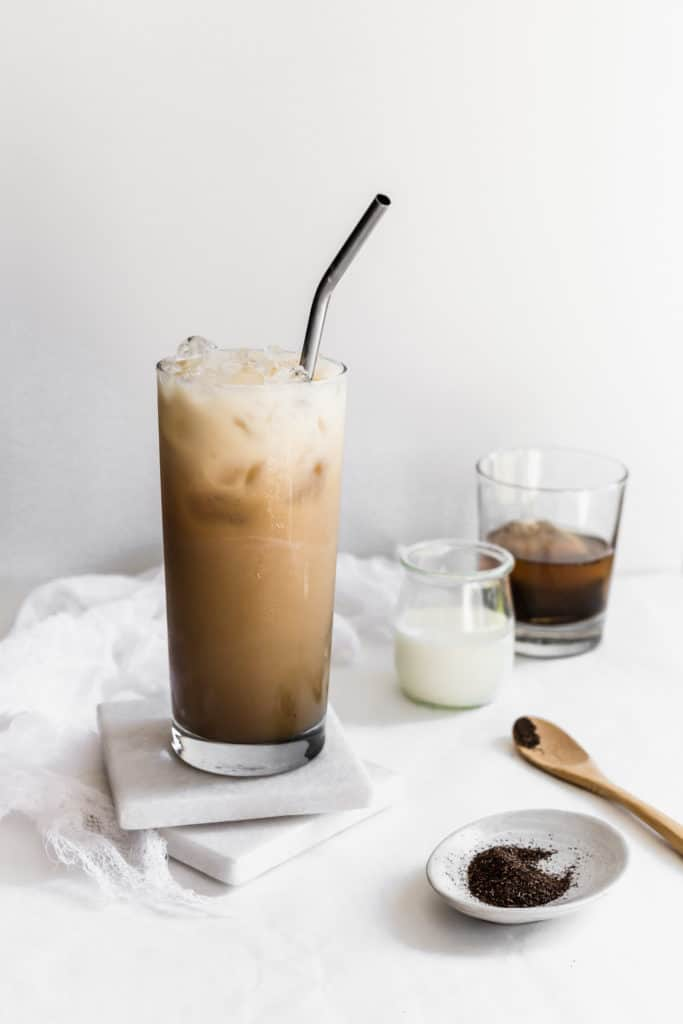 Glass of iced hojicha tea with straw on marble coasters, tea powder and milk on side.
