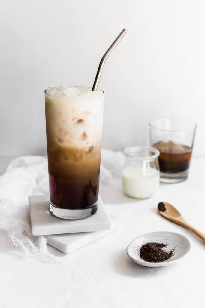 Glass of layered iced hojicha tea with straw on marble coasters, tea powder and milk on side.