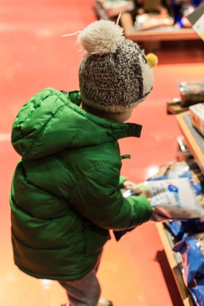 Kid grabbing package in grocery store.