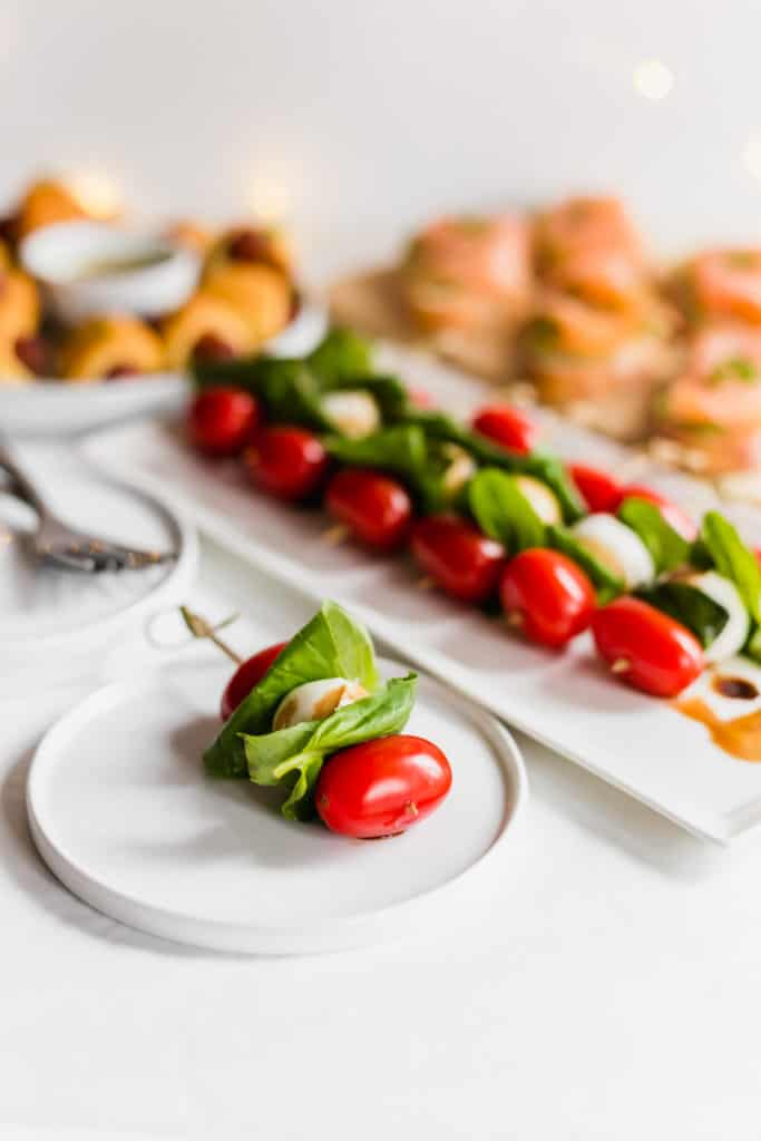 Bocconcini tomato basil skewer on small white plate, variety of appetizers in background.