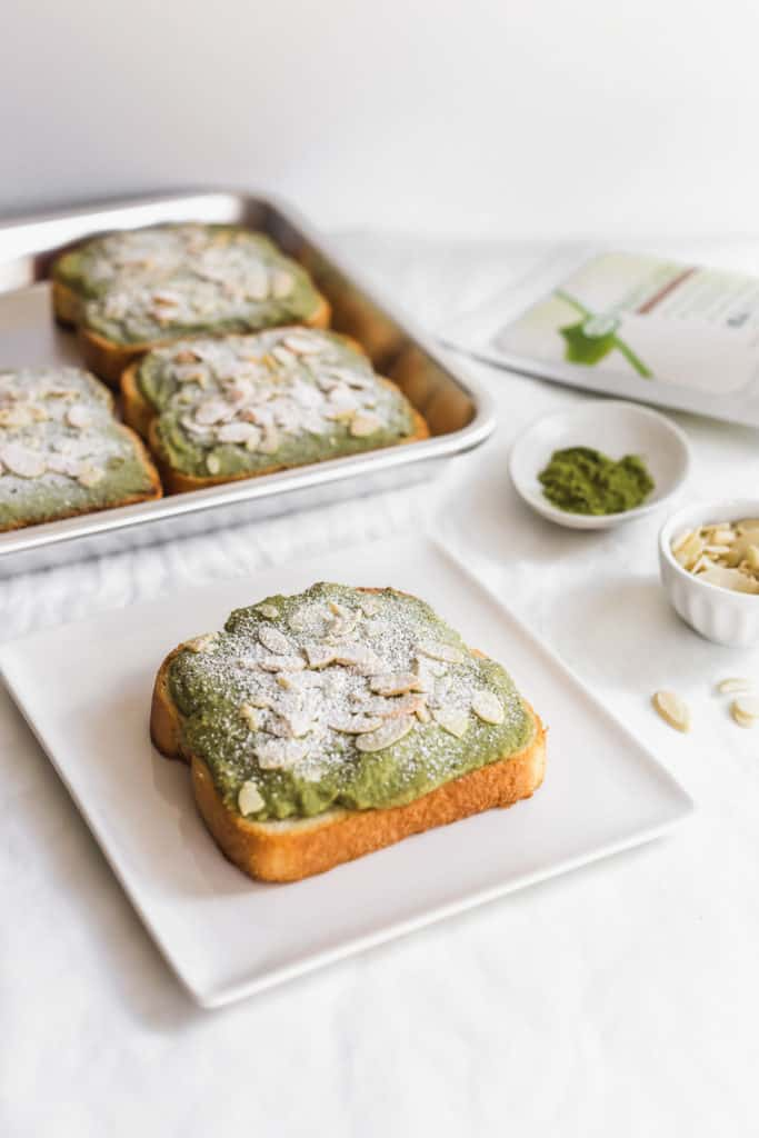 Matcha almond bostock on square plate, bostock on a tray, matcha powder and flaked almonds on the side.