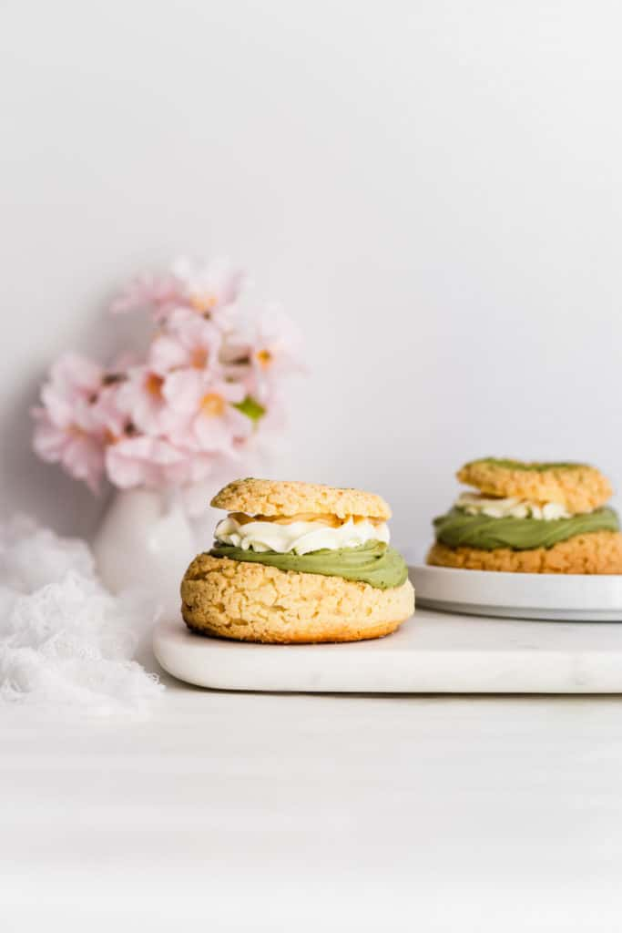 Cream puff with layer of matcha cream and whipped cream on top on marble board.