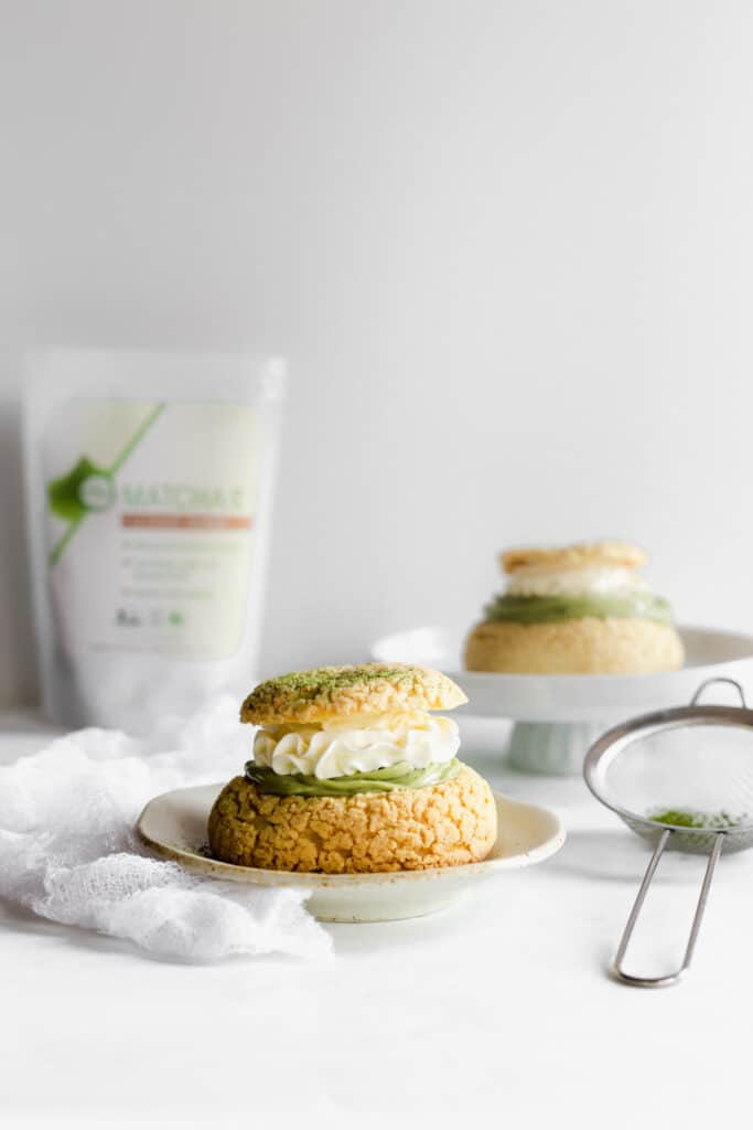 Cream puff with layer of matcha cream and whipped cream on top on small plate, sieve, tea packaging in background.