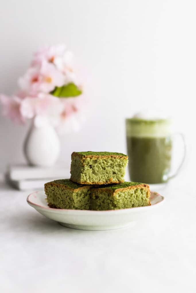 A stack of matcha almond brownies on a small plate, matcha latte in background.