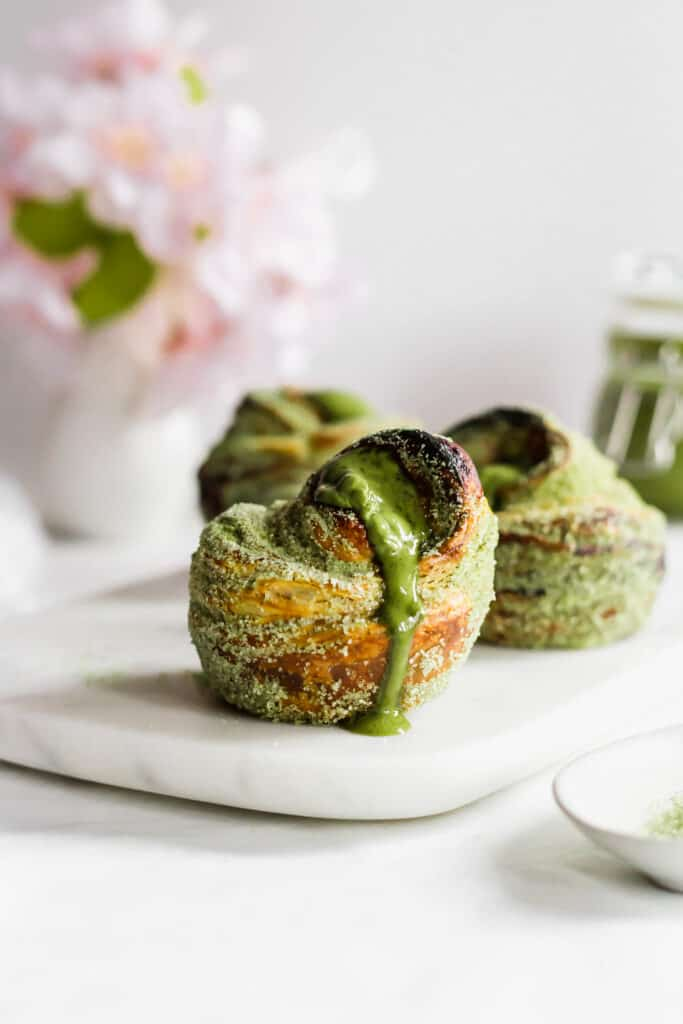 A close up of matcha cruffins with oozying matcha jam on marble board.