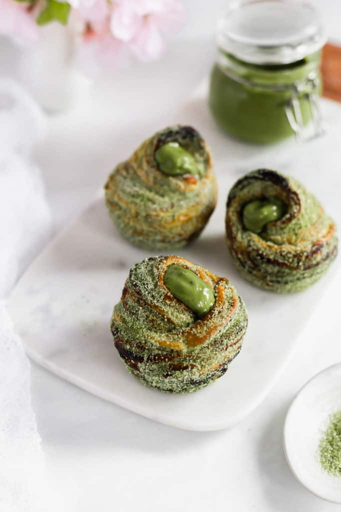 A group of matcha cruffins on marble board, jar of matcha milk jam in background.
