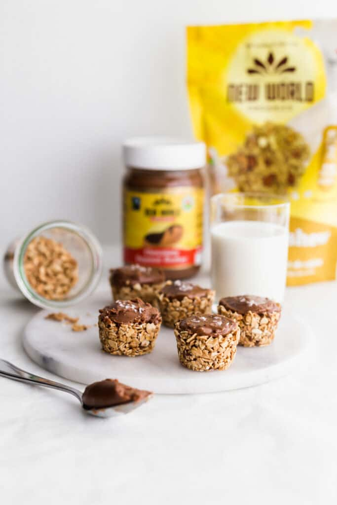 A group of granola chocolate peanut butter cups on marble round trivet, spoon filled with chocolate peanut butter on the side, jar of oats spilling out, with glass of milk, packaging in background.