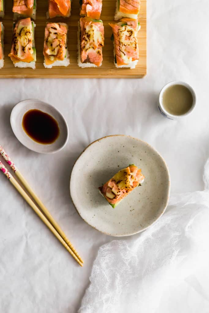 Aburi salmon sushi on beige plate with chopsticks, soy sauce on side.