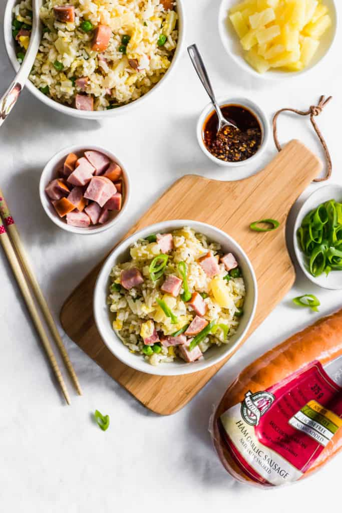 A bowl of fried rice on wooden board, meat packaging, green onions, diced ham in small bowl, diced pineapples on small plate, small bowl with spoon of hot sauce, and another bowl of fried rice with ladle.