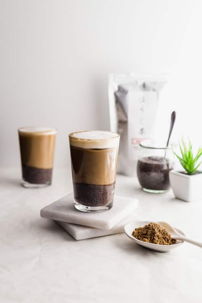 Glasses of layered hojicha black sesame oat latte on marble coasters with hojicha tea powder in foreground, tea packaging, black sesame paste in jar with spoon in background.