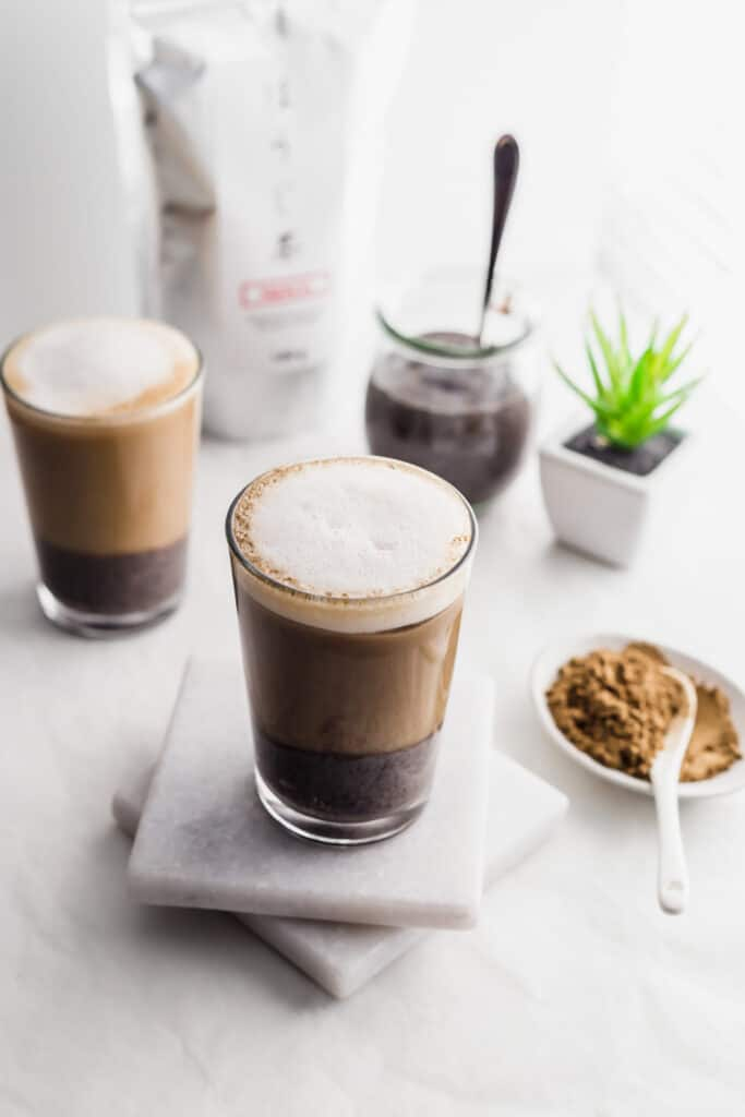 Glasses of layered hojicha black sesame oat latte on marble coasters with hojicha tea powder in foreground, tea packaging and black sesame paste in jar with spoon in background.