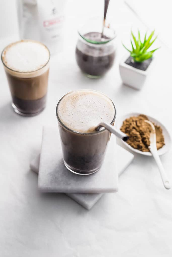 Glasses of layered hojicha black sesame oat latte with straw on marble coasters with hojicha tea powder in foreground, tea packaging and black sesame paste in jar with spoon in background.