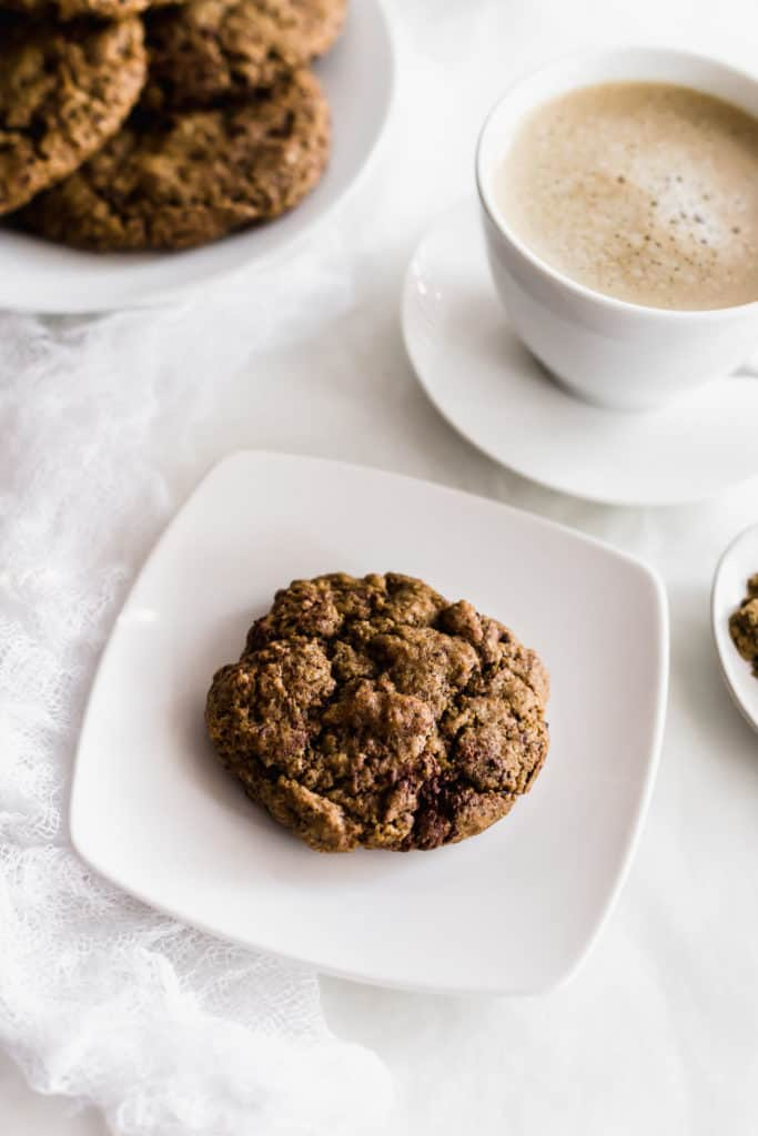 A hojicha espresso cookie on a white plate, cup of hojicha and plate of cookies in background.