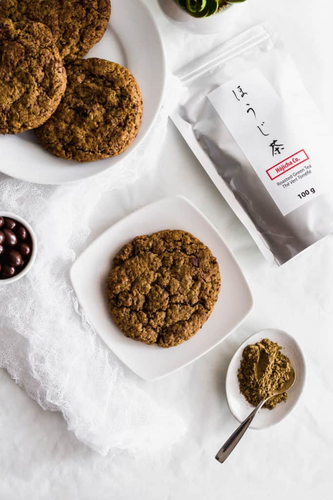 A hojicha espresso cookie on a white plate, hojicha powder with small spoon in a dish, tea packaging, plate of cookies