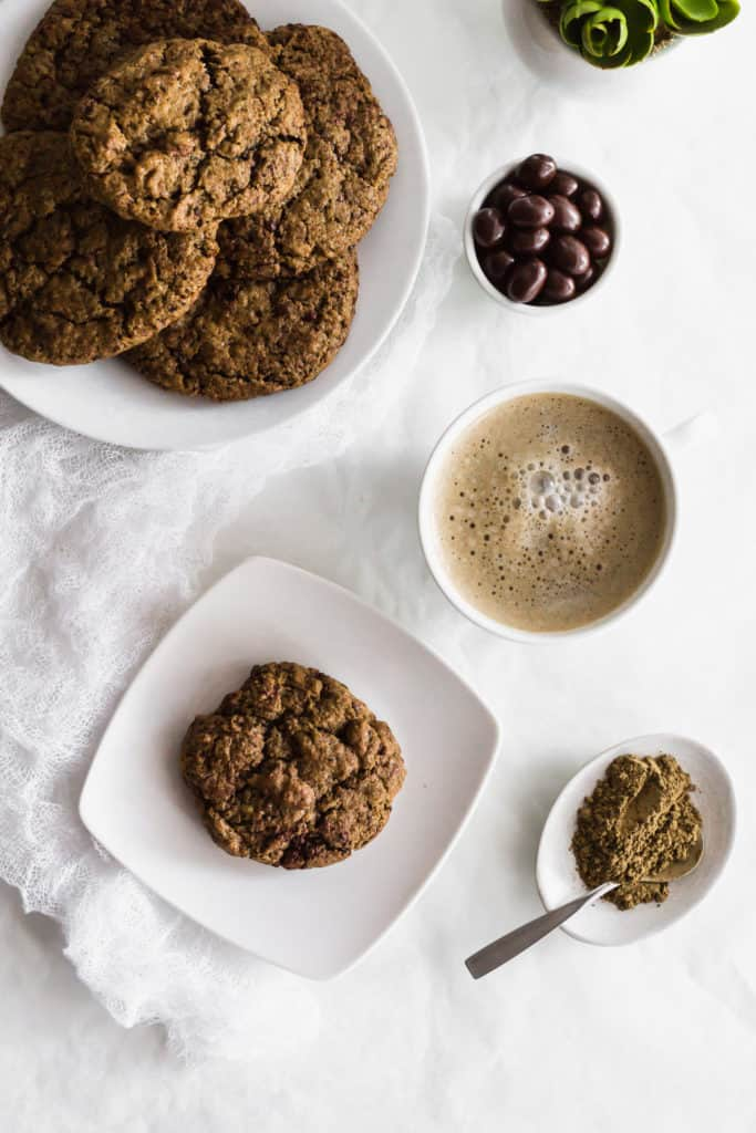 A hojicha espresso cookie on a white plate, cup of hojicha, espresso beans in a bowl, hojicha powder in a small dish with spoon, and plate of cookies on round plate.