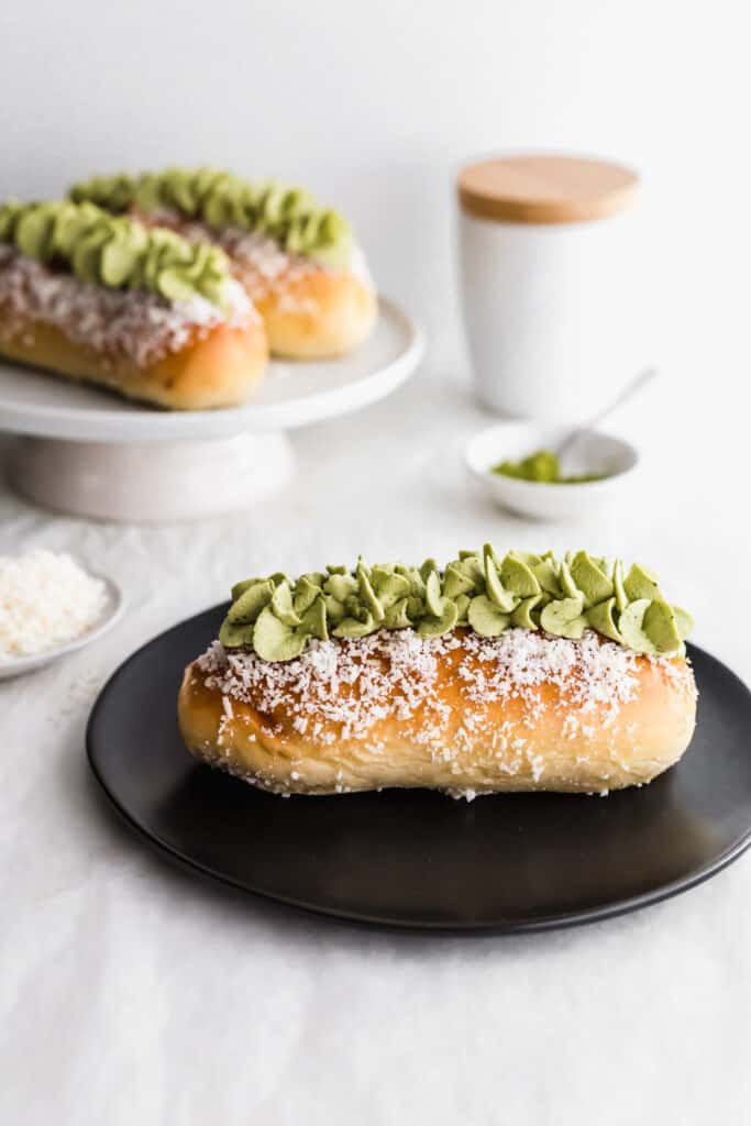 A close up of coconut bun with matcha cream on a black round plate, matcha in small dish with spoon, buns in background