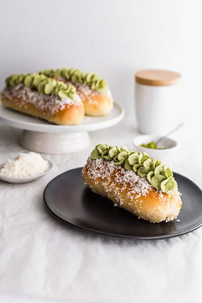 Matcha coconut cream bun on black plate.