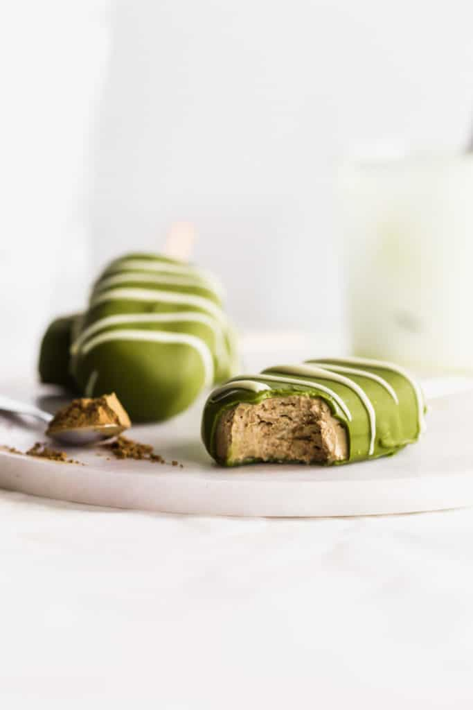 A matcha hojicha ice cream bar with a bite taken out of it on a marble trivet, spoonful of hojicha powder, ice cream bars in background.