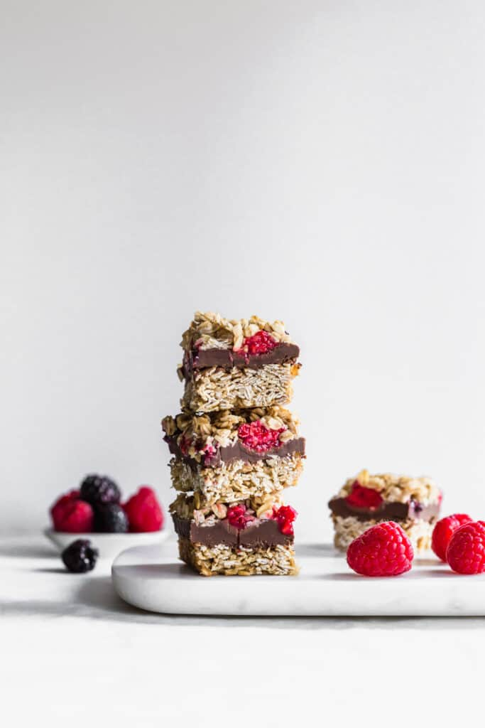 Stack of 3 SunButter chocolate raspberry oat bars on marble with fruit scattered.