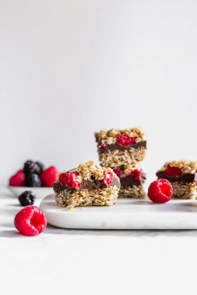 A bitten SunButter chocolate raspberry oat bar on marble with fruit scattered, a stack of bars in background.