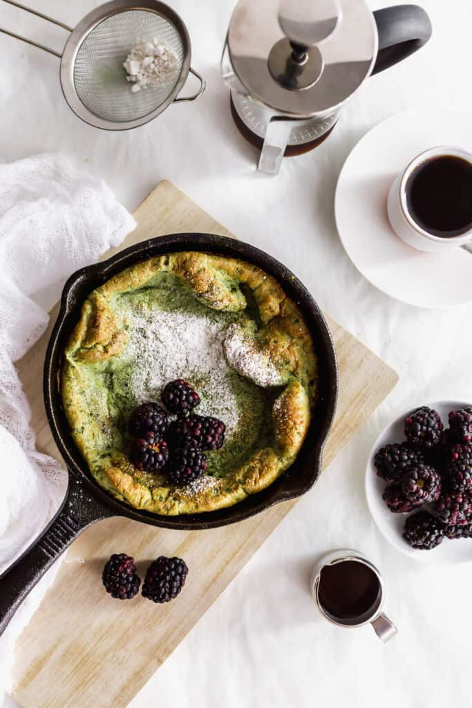 A matcha dutch baby with blackberries and powdered sugar in cast iron skillet on wooden board, with blackberries in a small plate, coffee, syrup on the side.