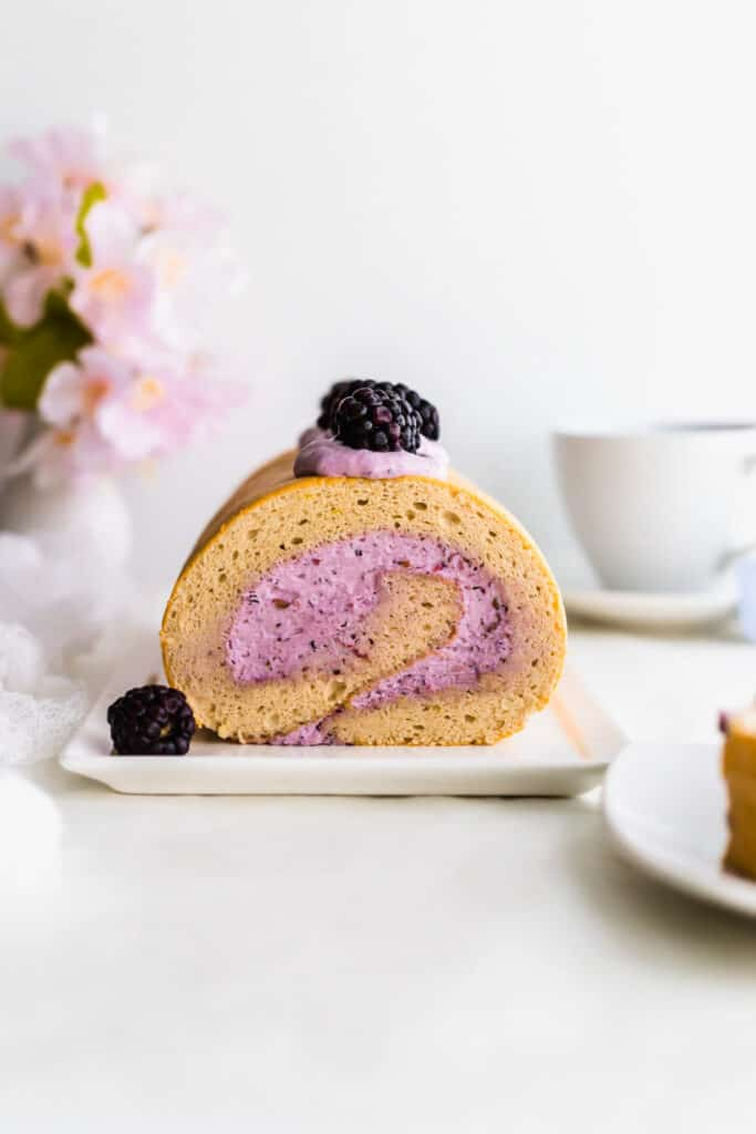 A close up of blackberry earl grey roll cake with purple cream on white rectangular plate, tea cup in background.