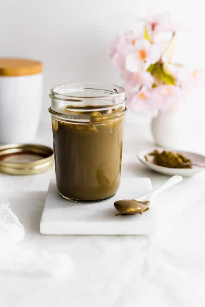 Jar of Hojicha Roasted Green Tea Milk Jam on marble coaster, spoon on side.