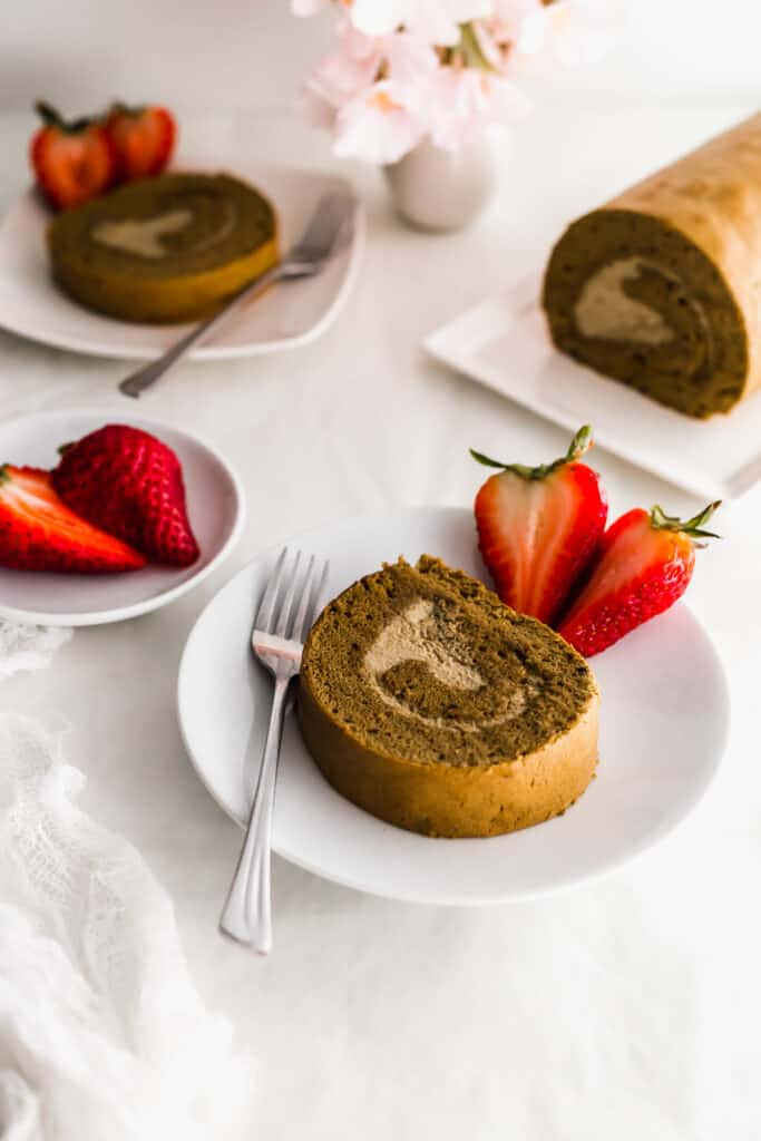 A slice of hojicha roll cake on a round plate with fork and cut strawberries, strawberries, and uncut cake in the background.