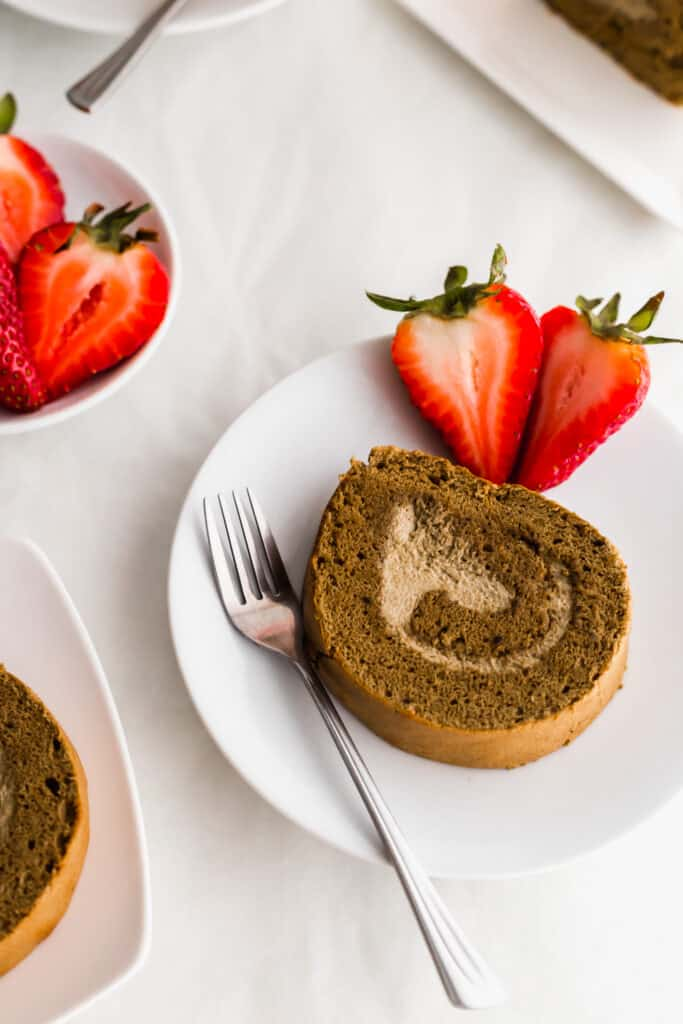 A slice of hojicha roll cake on a round plate with fork and cut strawberries.