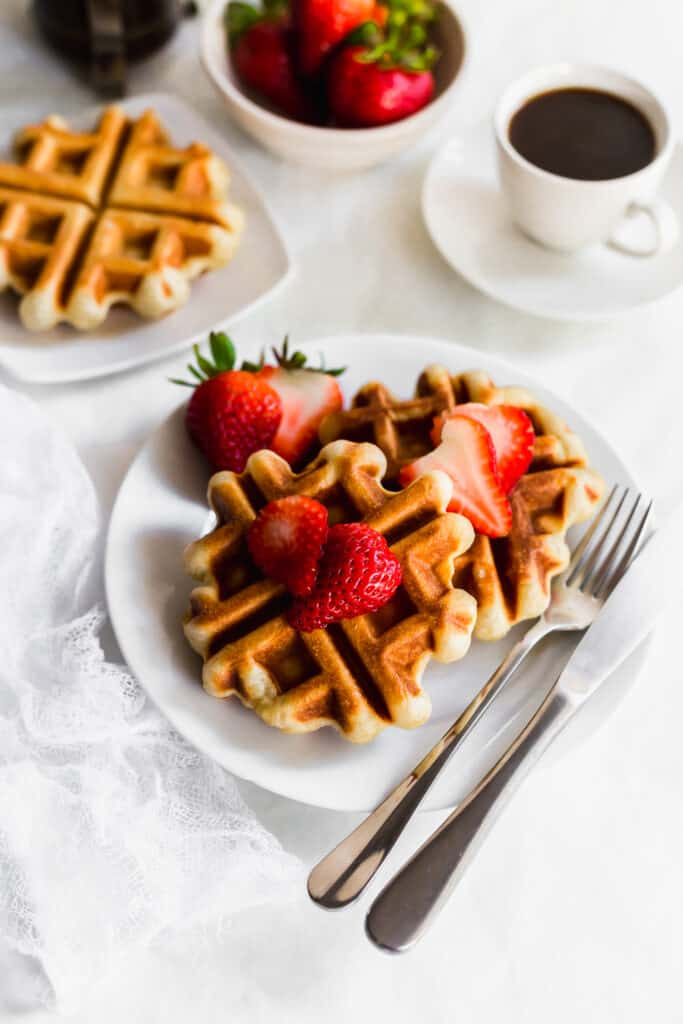 Sourdough liege waffles with strawberries on a white plate with fork and knife, cup of coffee and a bowl of strawberries in background.