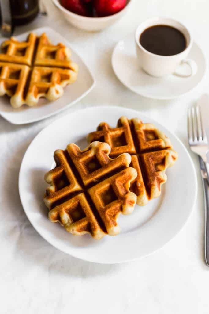 Sourdough liege waffles on a white plate with fork on side, cup of coffee.