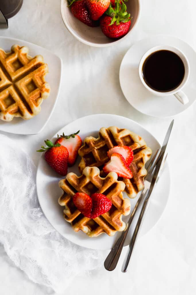 Sourdough liege waffles with strawberries on a white plate with fork and knife, cup of coffee and a bowl of strawberries.