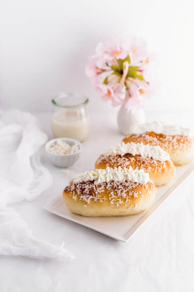 Coconut cream buns on rectangular plate.