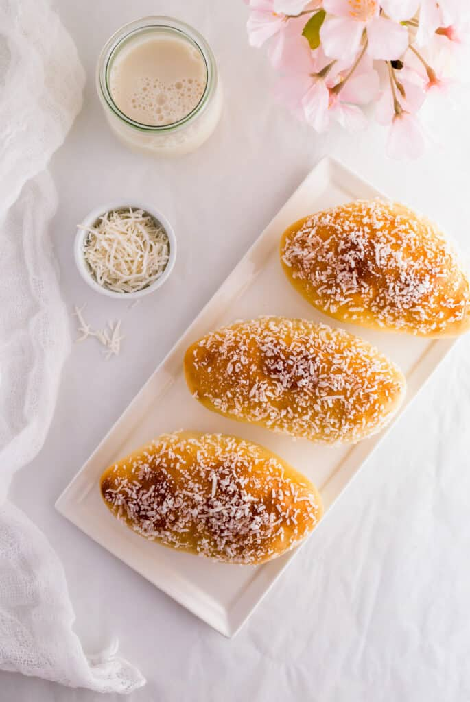 Unfilled coconut cream buns on white rectangular plate.