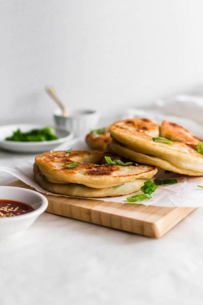 Green onion pancakes on a parchment on top of wooden board with green onions on a plate, hot sauce on the side, salt in a small bowl in background.
