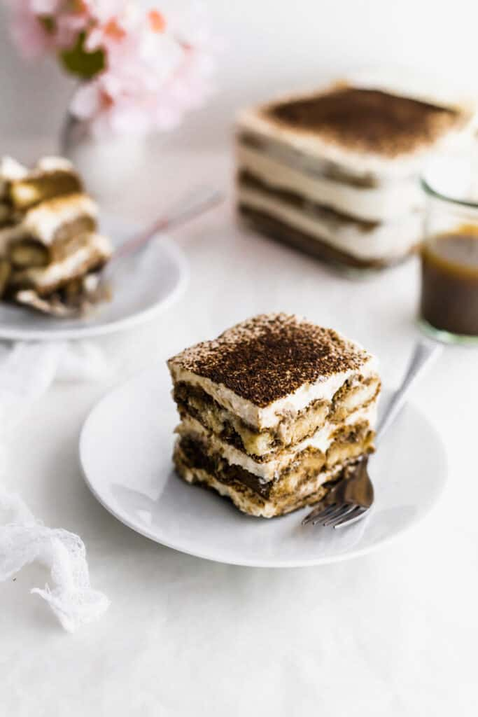 A slice of hojicha tiramisu on a white plate with fork with tiramsiu in container in the background.