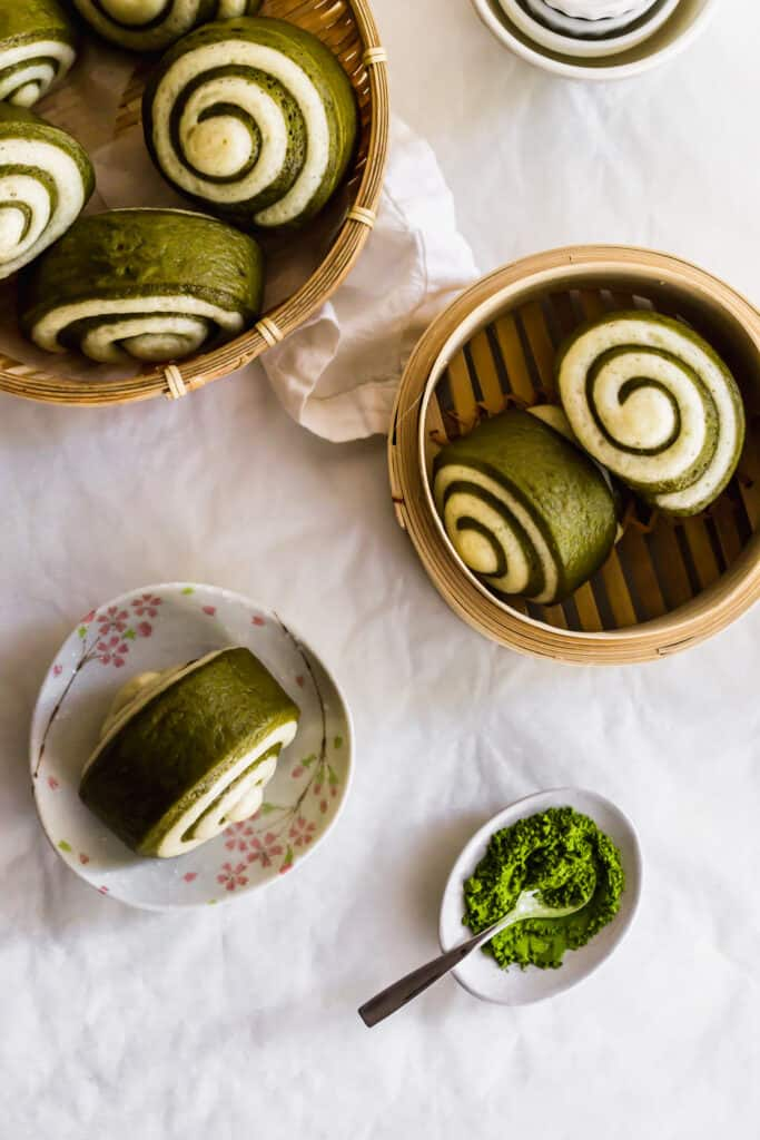 Swirled green and white matcha mantou bun on small plate with more buns in bamboo steamers, green matcha tea in a small plate with spoon..