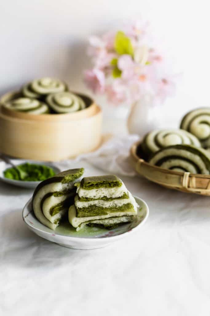 Torn green and white matcha mantou bun revealing interior on small plate with matcha tea, more buns in bamboo steamers in background.