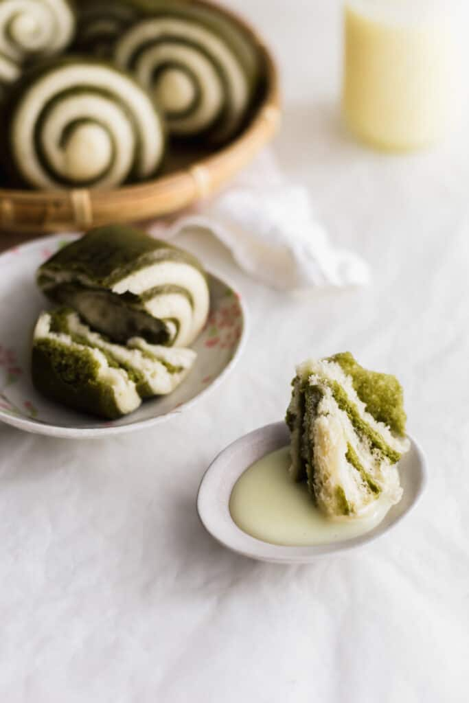 A close up of torn green and white mantou bun dipped in condensed milk on a small plate, ripped bun on a plate in background.