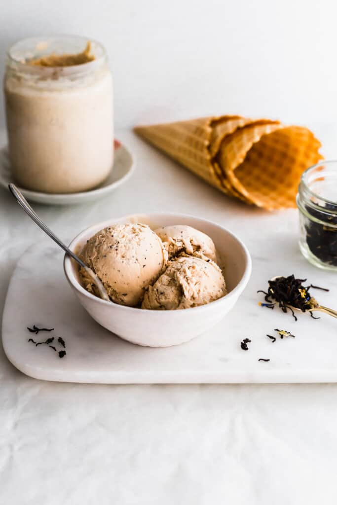 Scoops of ice cream in a bowl with a spoon on marble with earl grey tea in a jar scattered around, jar of ice cream, waffles cones in background.