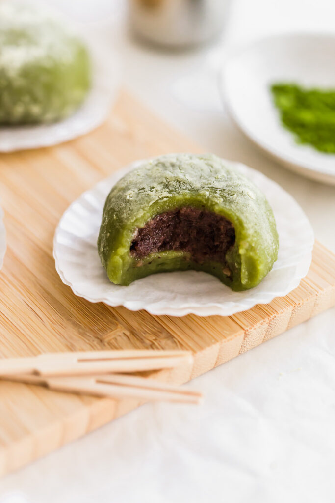 Bitten matcha mochi on cupcake liners on wooden board revealing red bean paste inside, toothpicks in foreground, matcha powder in the background.